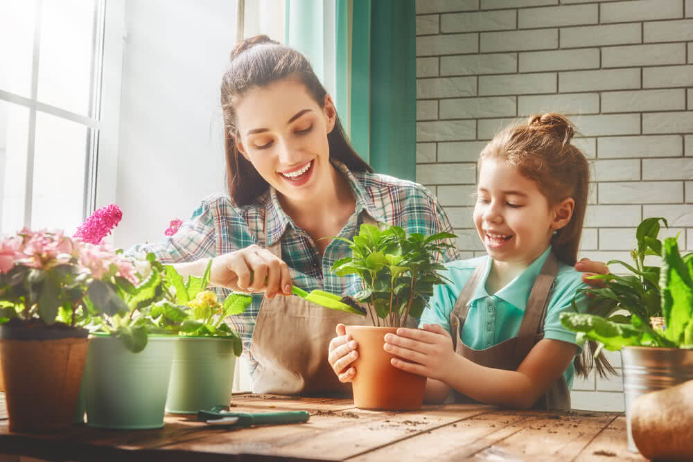 mother teaching her daughter about how to care for plants