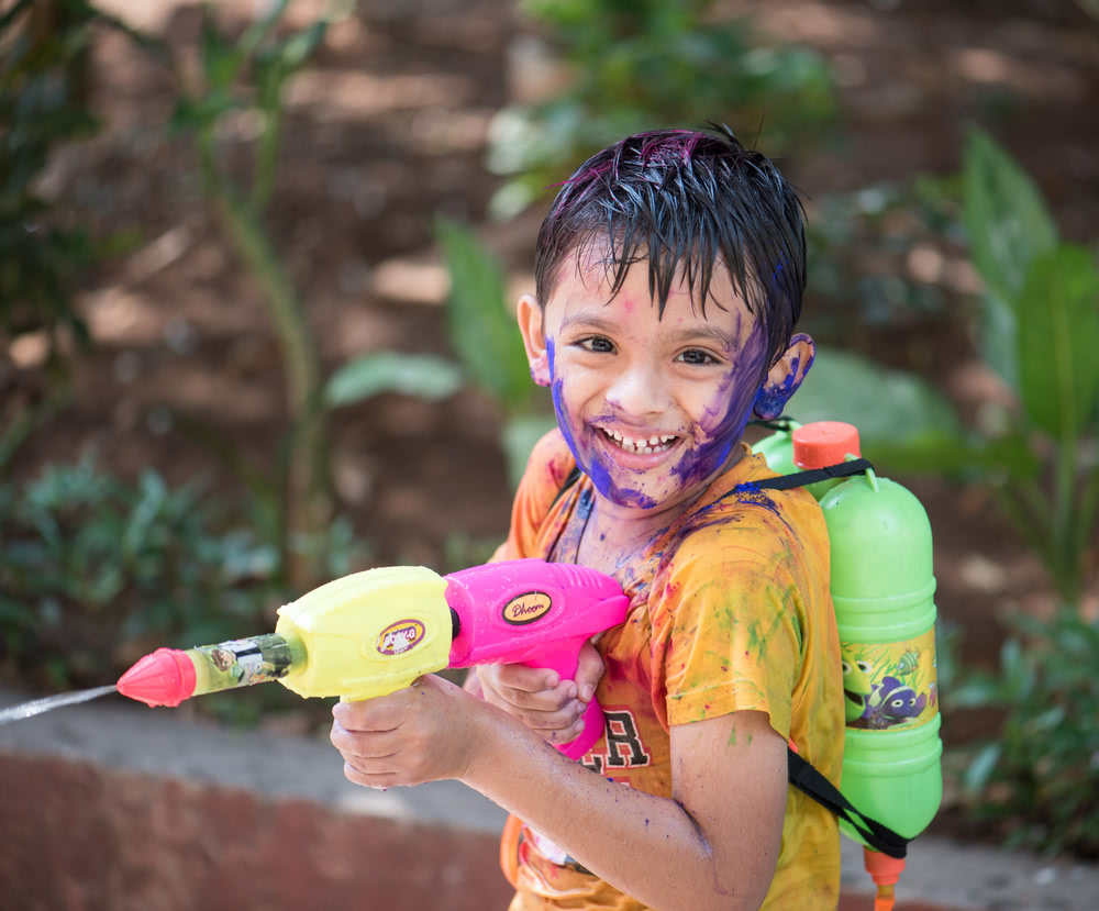 Boy on Indian color festival playing with water gun